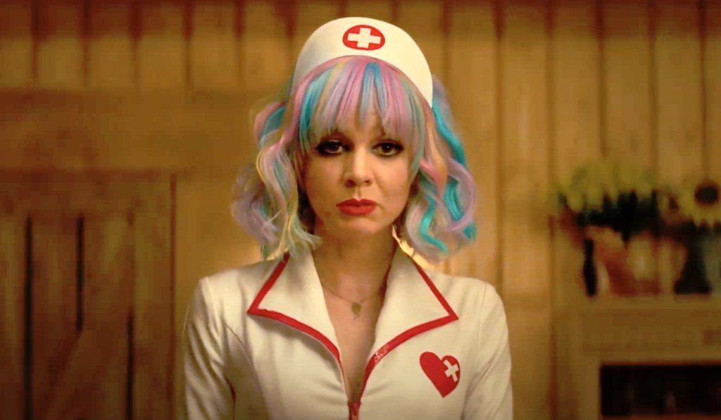 A young white woman with rainbow-striped hair in a nurse's costume stares grimly forward.