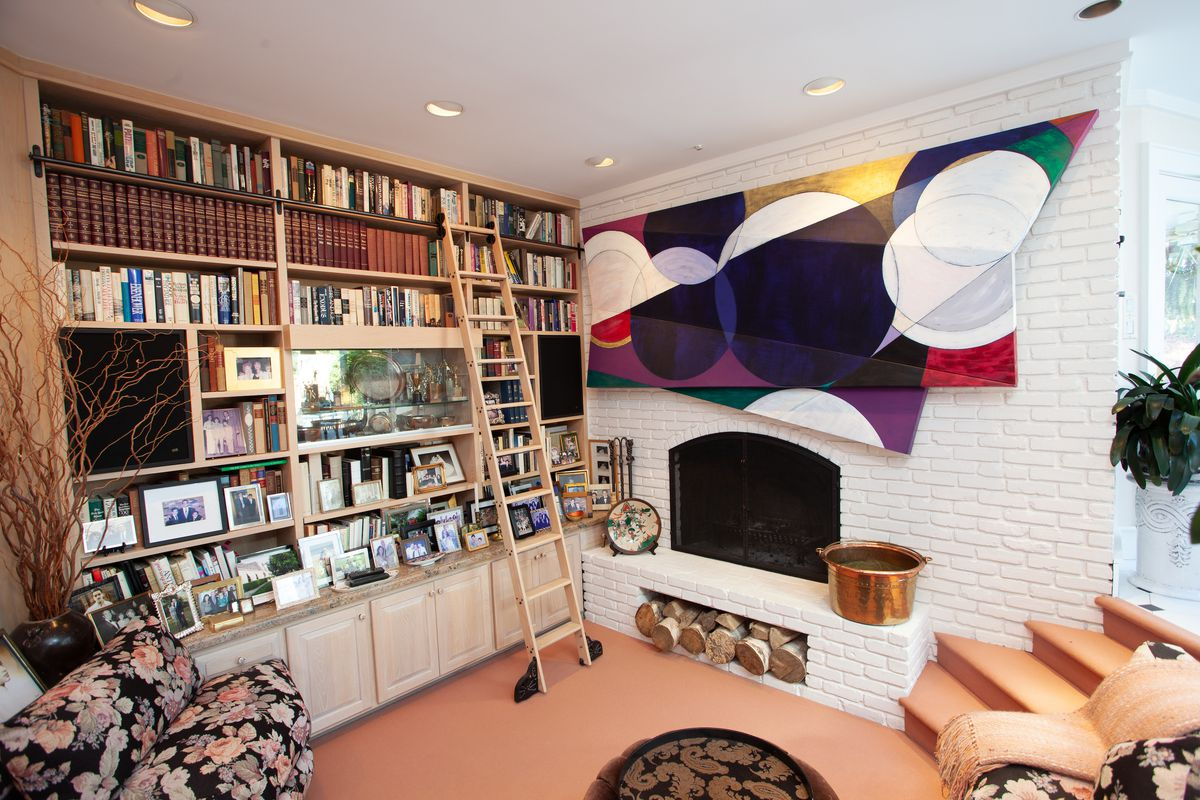 A conversation pit with white bricked fireplace, built-in bookshelves, and a large abstract painting above the fireplace.
