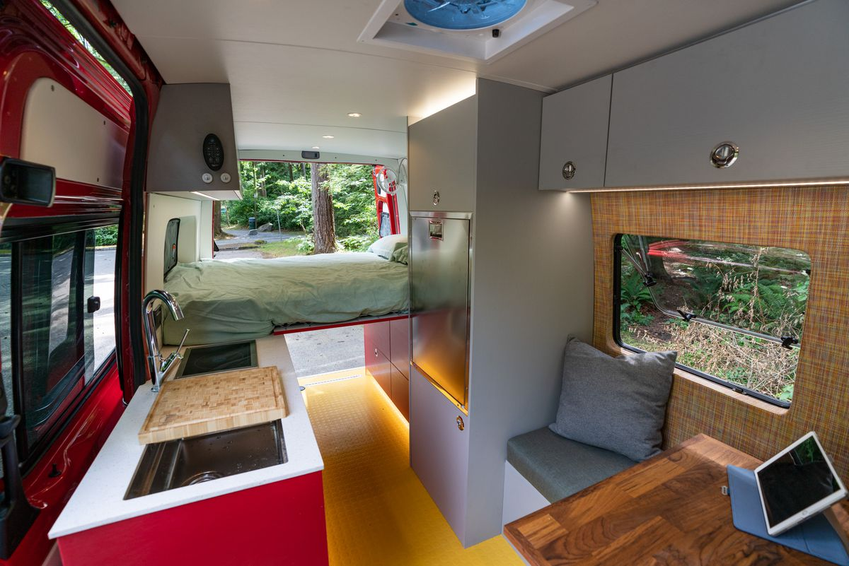 The interior of a camper van features yellow floors, red cabinets, white countertops, a wooden table, and gray upper cabinets for storage. The rear of the van boasts a bed.