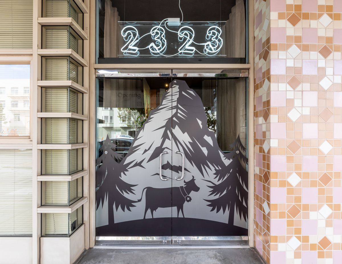 A door with a cow and a mountain sketched on it