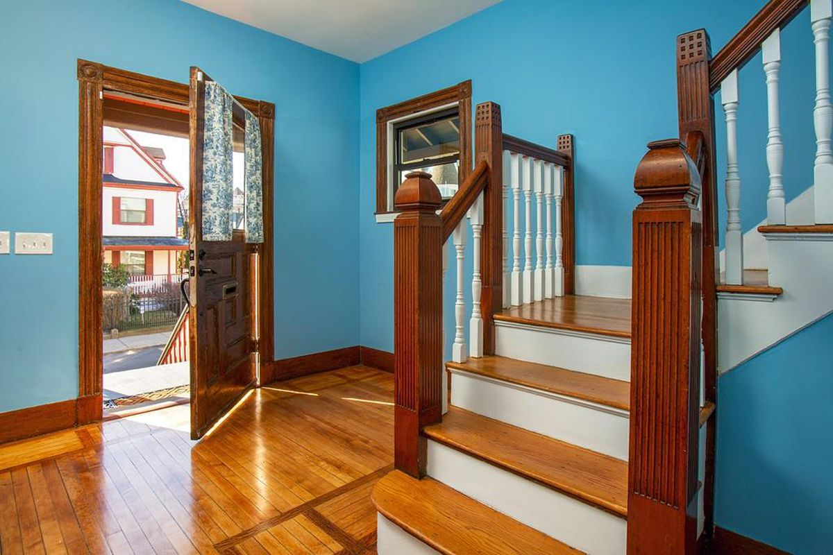 A colorful, spacious foyer just beyond an open front door and next to a staircase.