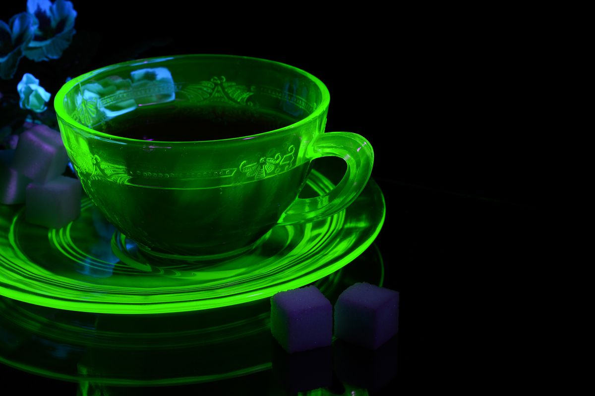 A glass tea cup glows green under UV light due to the uranium content.