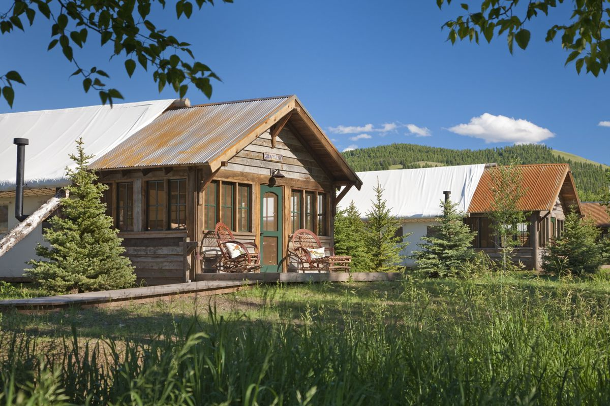 Cabins with a combination wooden and canvas exterior. In the foreground is tall wild grass.