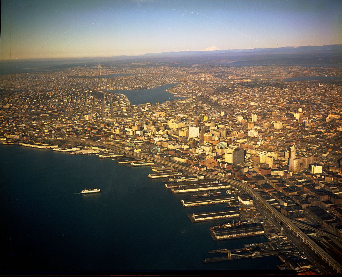 An aerial view of the Seattle waterfront. There is a large body of water adjacent to many buildings.