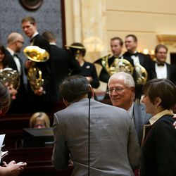 Senators greet one another as the Utah Valley University Horn Choir poses for a photo during the first day of the Utah Legislature at the Capitol in Salt Lake City on Monday, Jan. 25, 2016.