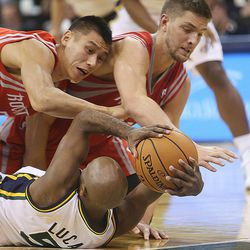 Utah Jazz's point guard John Lucas III (5) tries to regain control of the ball as Houston's Jeremy Lin and Chandler Parsons fall on him as the Jazz and the Rockets play Saturday, Nov. 2, 2013 in EnergySolutions arena. Jazz lost 104-93.