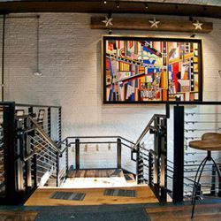 """The artwork over the staircase is titled """"The Mechanical Period"""" by Andre De Moeller and is meant to honor those who helped restore the building."""