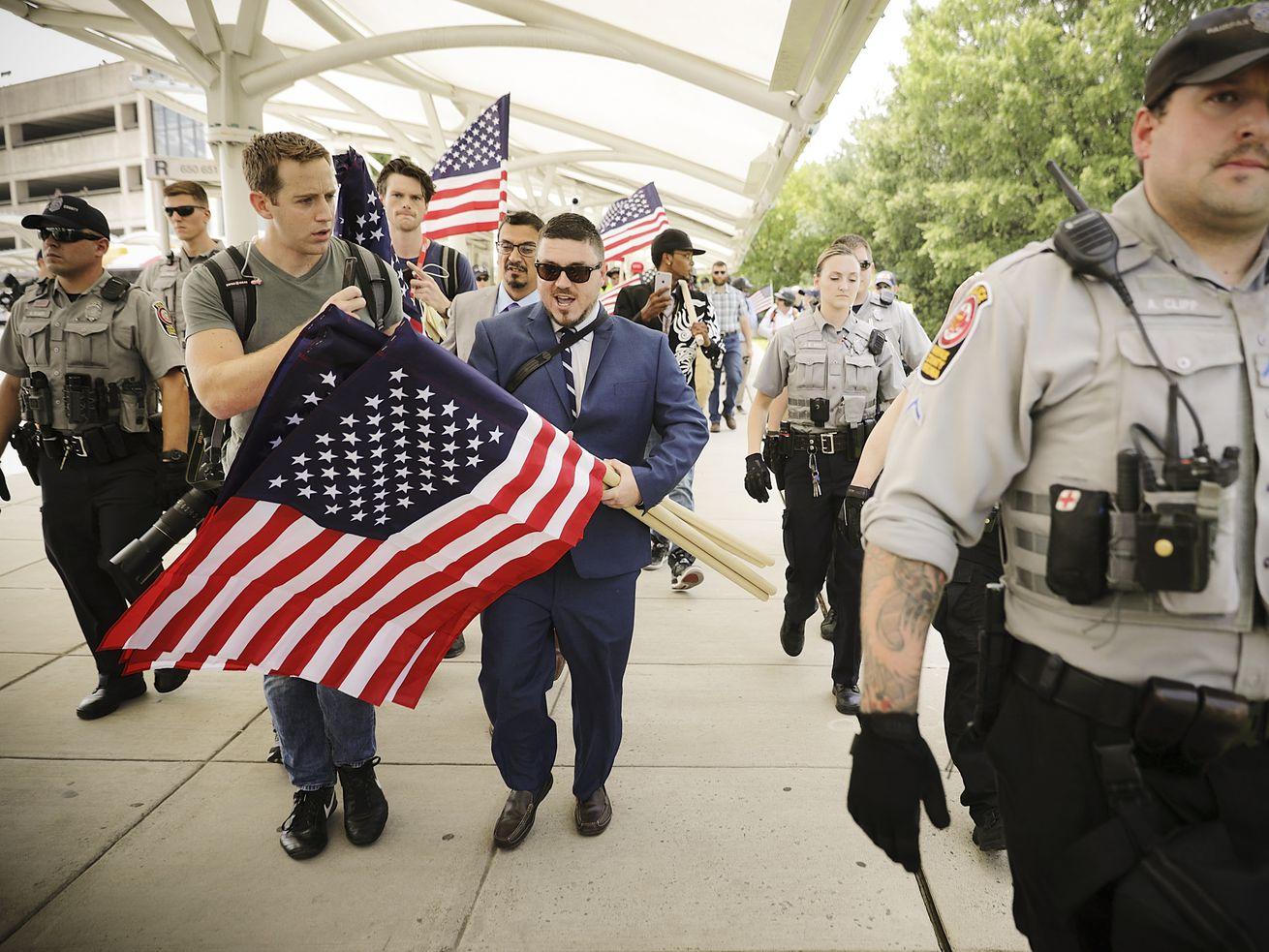 "Surrounded by supporters, reporters and Fairfax County Police, Jason Kessler (center) walks toward the Vienna/Fairfax GMU Metro Station to travel by train to the White House for his white supremacist ""Unite the Right"" rally on August 12, 2018, in Vienna, Va."