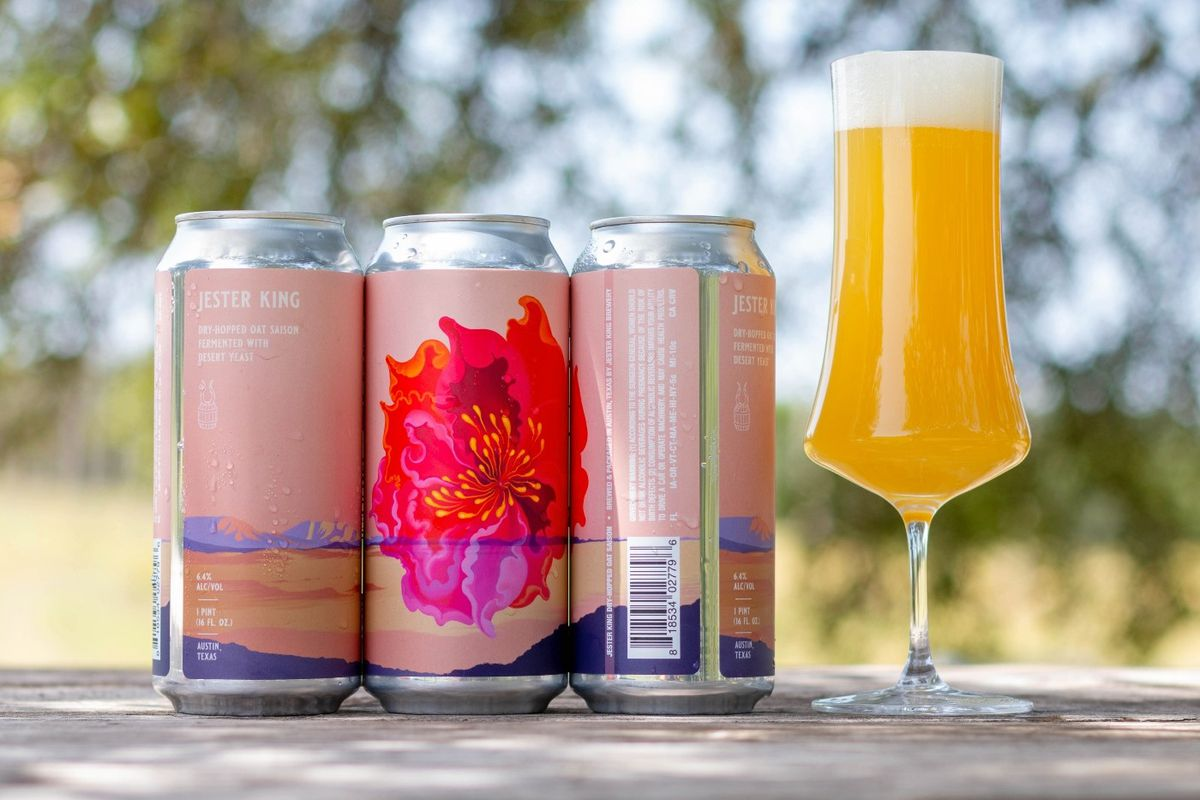 """Three tall cans of beer with pale pink labels, the can on the far left reads """"Jester King, Dry-Hopped Oat Saison with desert yeast,"""" and the middle can features a brighter pink flower, all next to a tall thinner beer glass with a golden liquid on top of a wooden table in front of trees"""