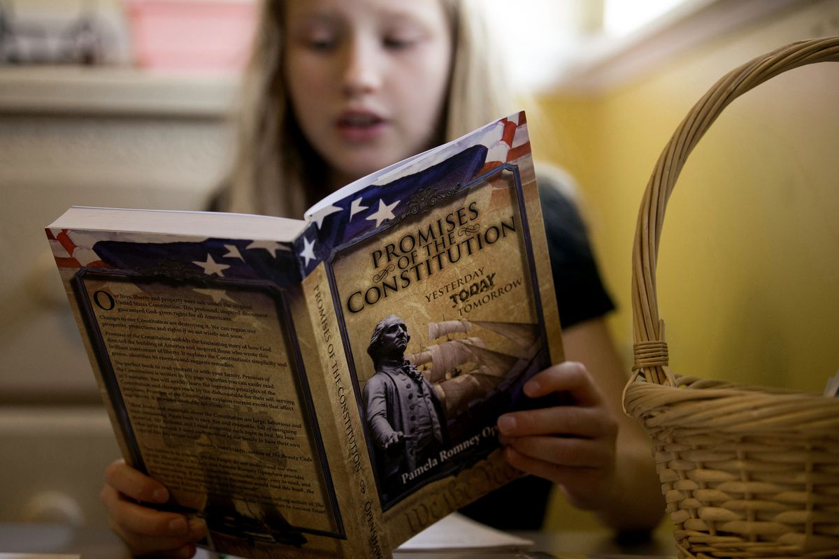 """Allison Brown, 8, reads from """"Promises Of The Constitution: Yesterday Today Tomorrow"""" by Pamela Romney Openshaw during home-schooling at her West Jordan home on Friday, Nov. 3, 2017."""