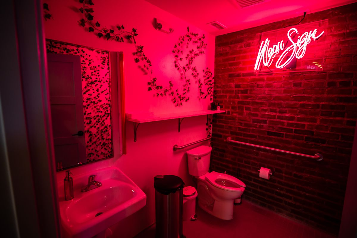 """The bathroom at Little Bear lit up in red light from the sign that reads """"Neon Sign"""" on the wall"""