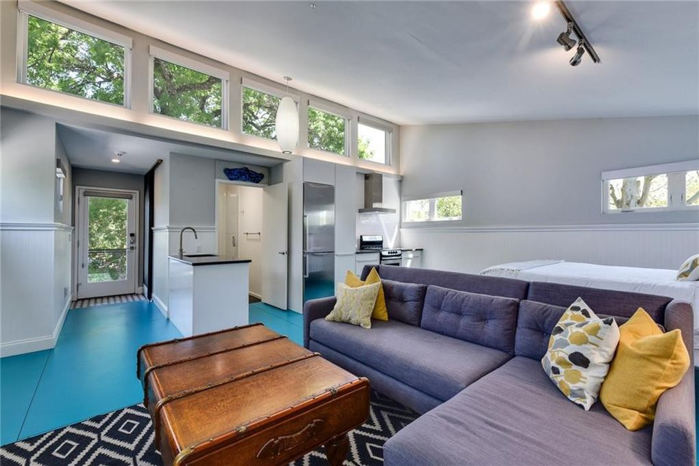 The guest house has an open concept floorplan, with a small kitchenette, a purple couch, a bed, and teal floors.