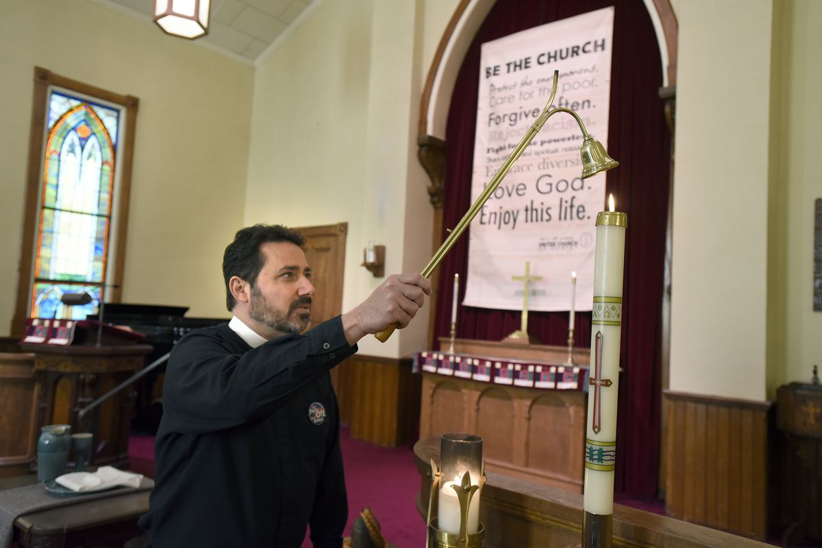 The Rev. Salvatore Sapienza puts out candles inside the historic Douglas Congregational United Church of Christ in the village of Douglas, Mich.,on Tuesday Oct. 13, 2020. As part of the Our Faith Our Vote 2020 initiative, volunteers at the church will drive voters with their completed mail-in ballots to the county clerk's office to drop them off in person. The drivers and voters will be masked and separated in vehicles to minimize any COVID-19 risk.