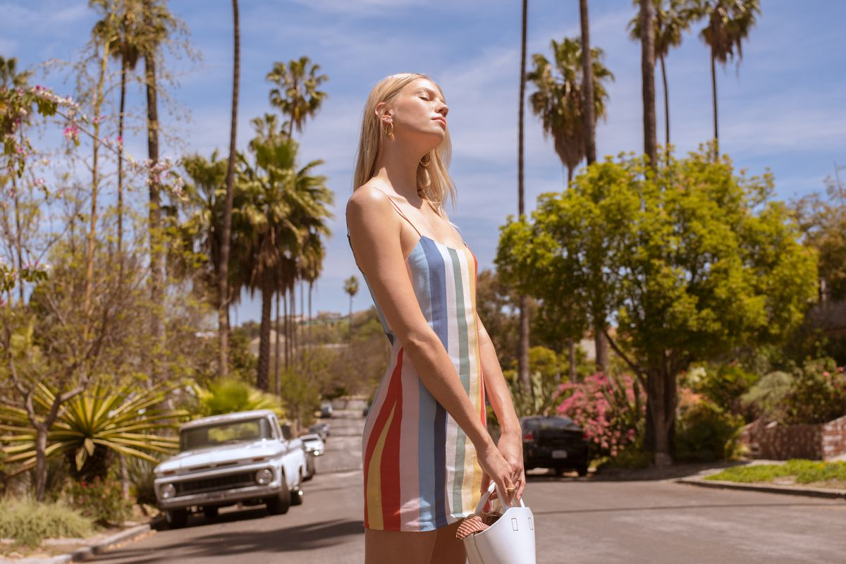 A model wears a rainbow-striped minidress, standing in the middle of a street in LA.