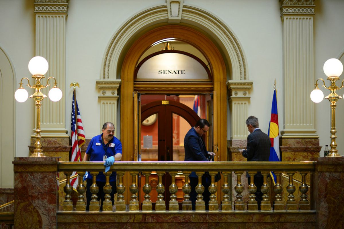 Janitor Chris Martinez, left, wipes down the handrails outside the Senate in the Colorado State Capital building in Denver, Colorado on March 13, 2020.