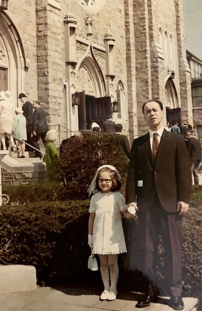 A little girl wearing glasses and a white dress stands next to an older man wearing a suit and red tie.