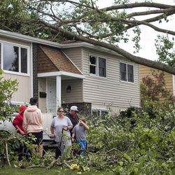 A family stands outside their home on Janes Avenue near Evergreen Lane in Woodridge after a tornado ripped through the western suburbs overnight, Monday morning, June 21, 2021.