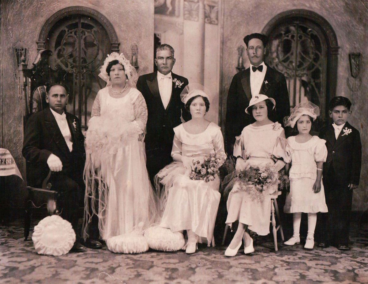 A posed photo of a Punjabi-Mexican family, the men in suits and tuxes and the women in formal white dresses and fancy hats