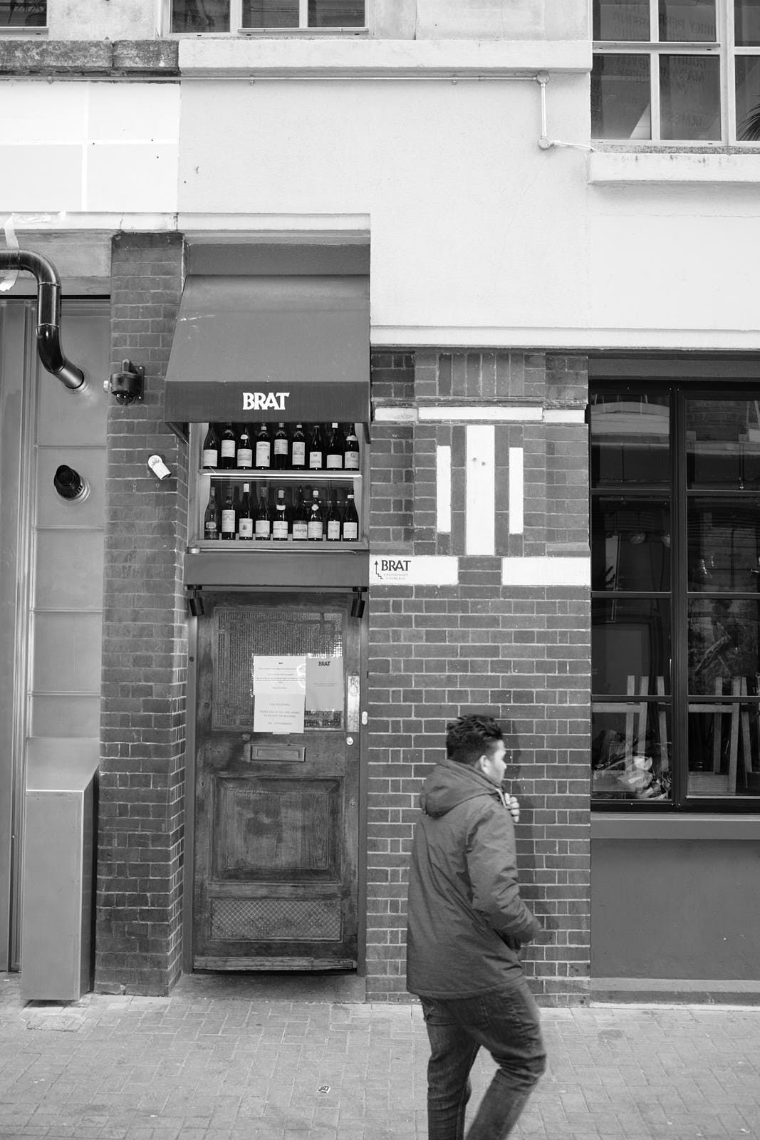 A man stands outside the entrance to Brat restaurant in Shoreditch, London