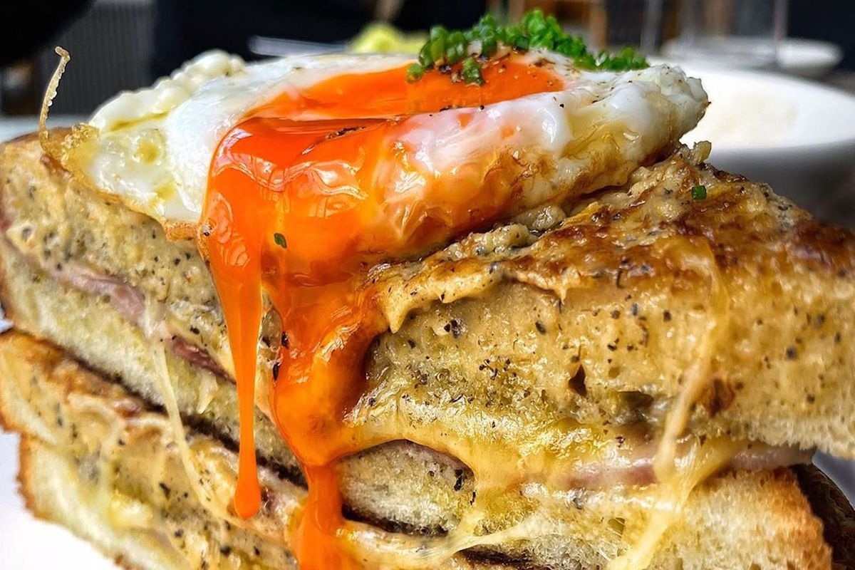 A croque madame toastie on a white plate with an egg yolk running down the sandwich