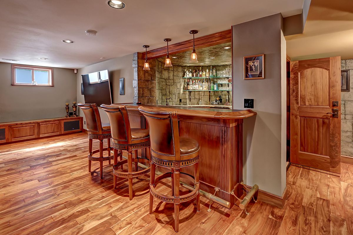 A stone alcove contains shelves of liquor. A wood bar separates it from the rest of the room.