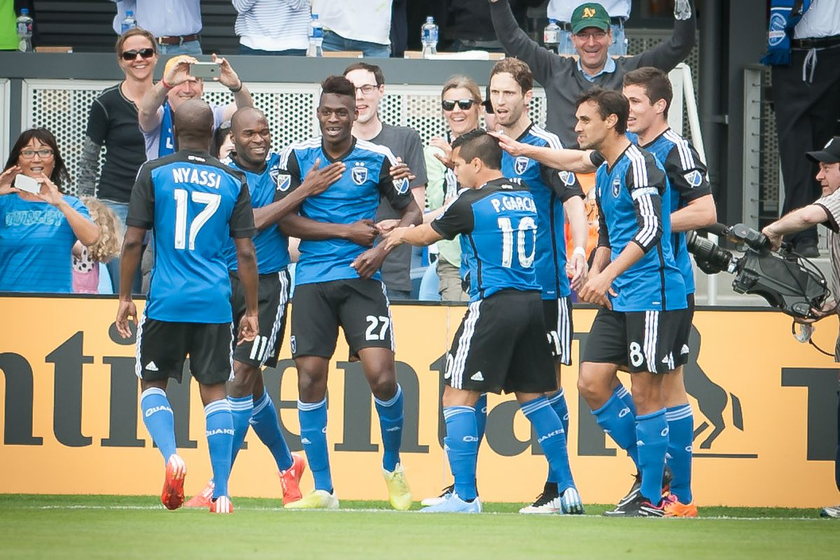 Fatai Alashe is mobbed by teammates after scoring the first-ever goal at Avaya Stadium