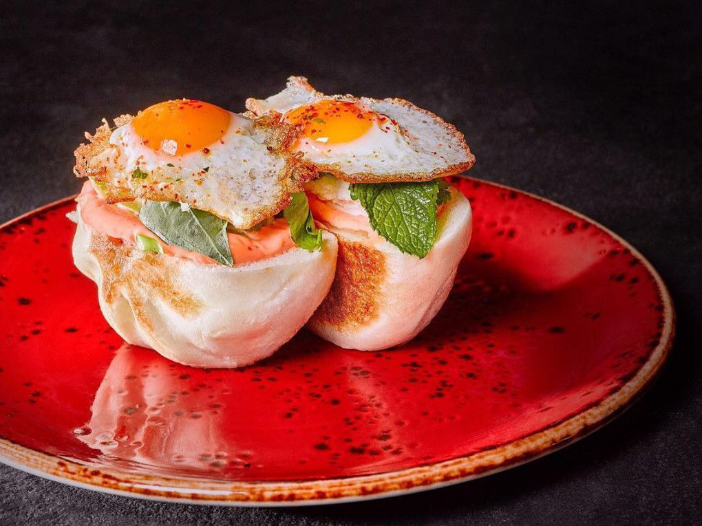 A red plate with two overflowing steamed pork buns topped with a garnish of greens and fried quail eggs.