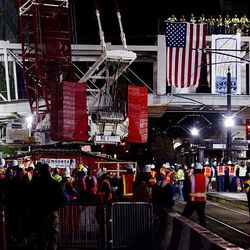 Construction workers gather on Main Street after a skybridge is secured in place connecting the City Creek Center development in downtown Salt Lake City Sunday.