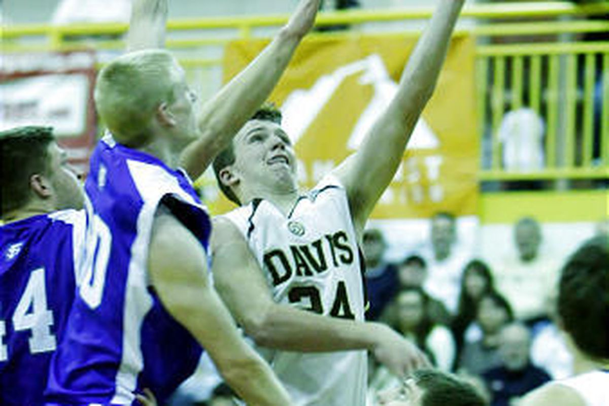 Davis' Tallon Burton, right, flies in for a layup around the defense of Fremont's Tate Lewis as Davis and Fremont play in Region 1 action. Davis won 62-44.