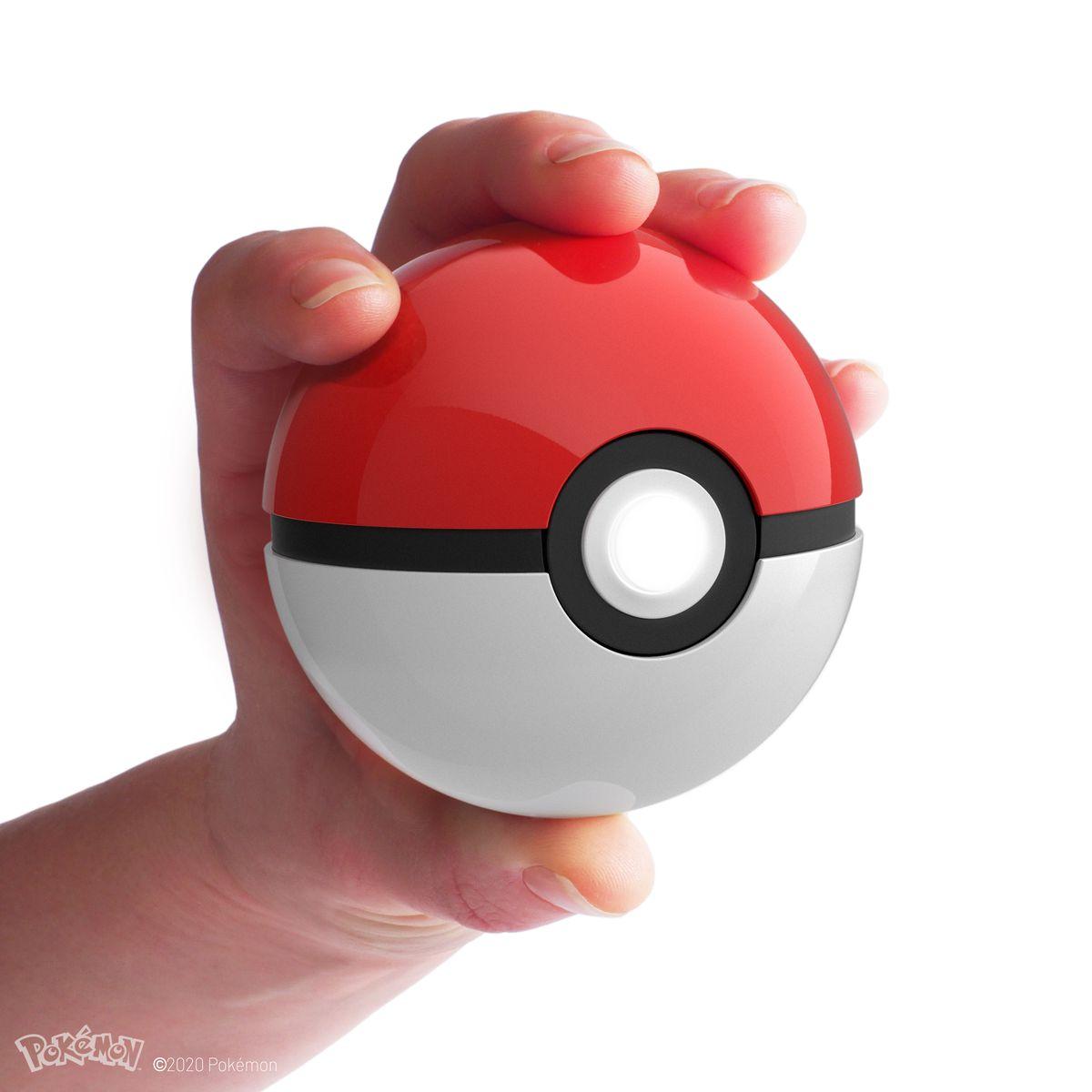 A hand holds a replica Poké Ball