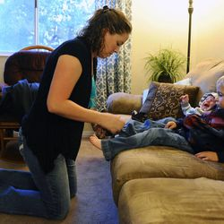 Mary Burton helps put on 3-year-old Logan's shoes to go outside as two-month-old Raiger cries next to Logan on the couch Sept. 25.