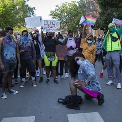 """Protestors hold up signs and raise their fists during the """"Drag March for Change"""" protest on Halsted Street in Lakeview, Chicago, Sunday June 14, 2020. Black drag community leaders led a protest march in support of Black Lives Matter and to demand justice for victims of police brutality."""