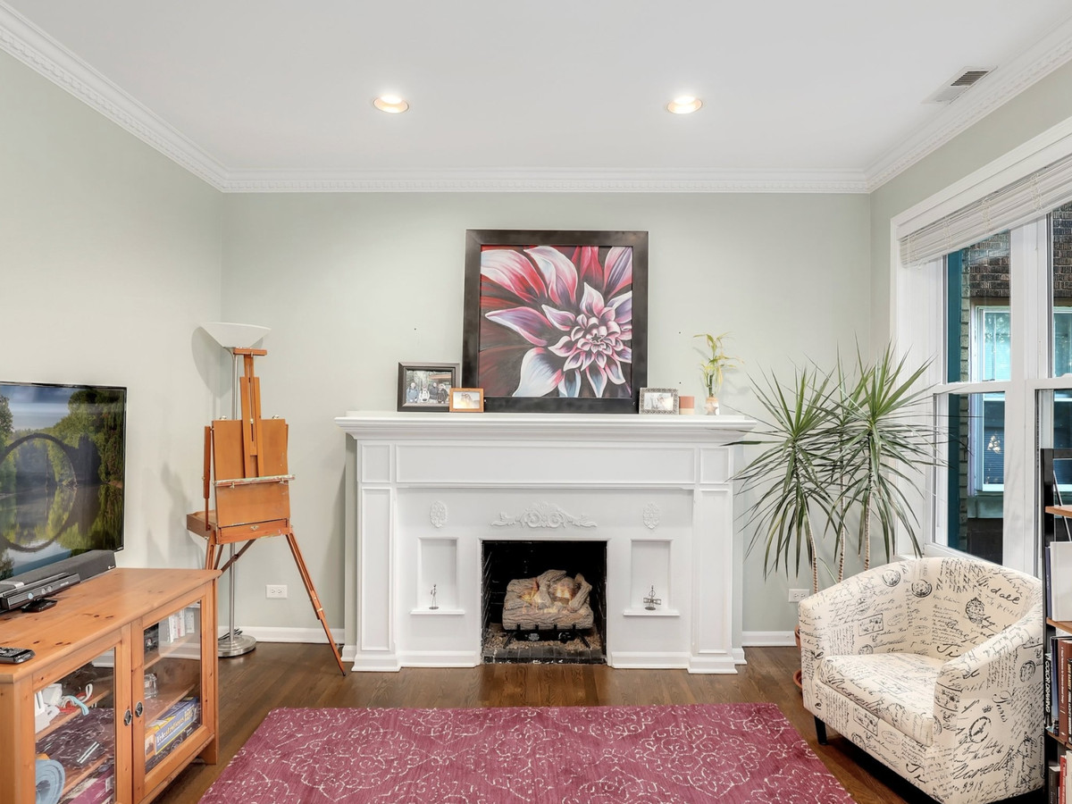 A white fireplace against a pale wall in a room with a red area rug, wood media console, across from an upholstered chair.