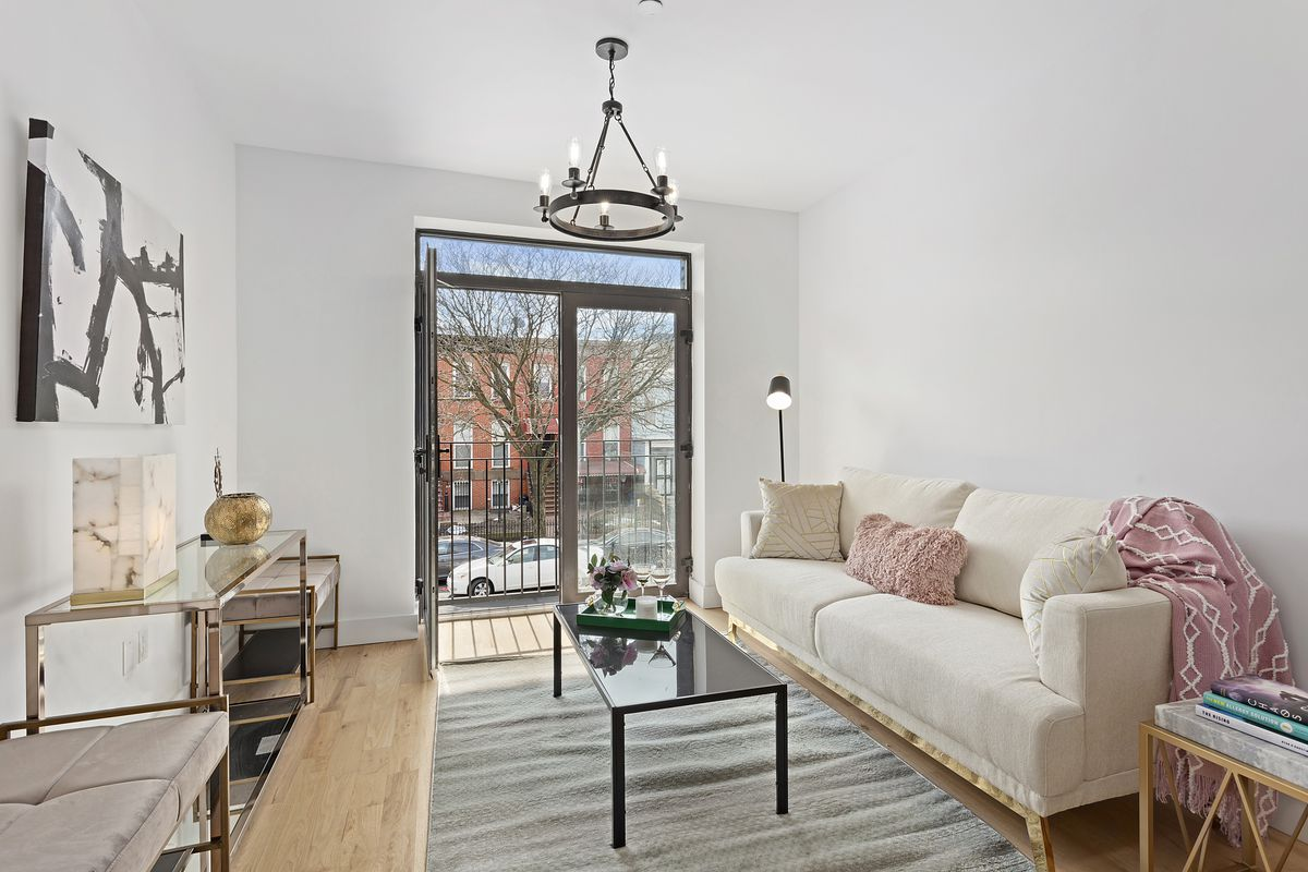 A living area with hardwood floors, white walls, a beige couch, and a glass door that leads to a balcony.