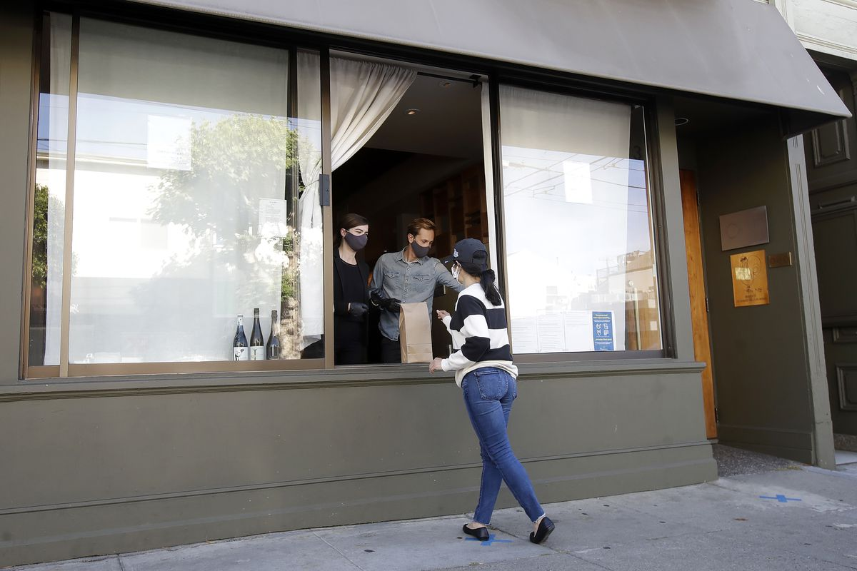 Lead sommelier Rachel Coe (left) and service manager Antoine Mueller wear face masks as they assist a customer at the Atelier Crenn restaurant window during the coronavirus outbreak in San Francisco.