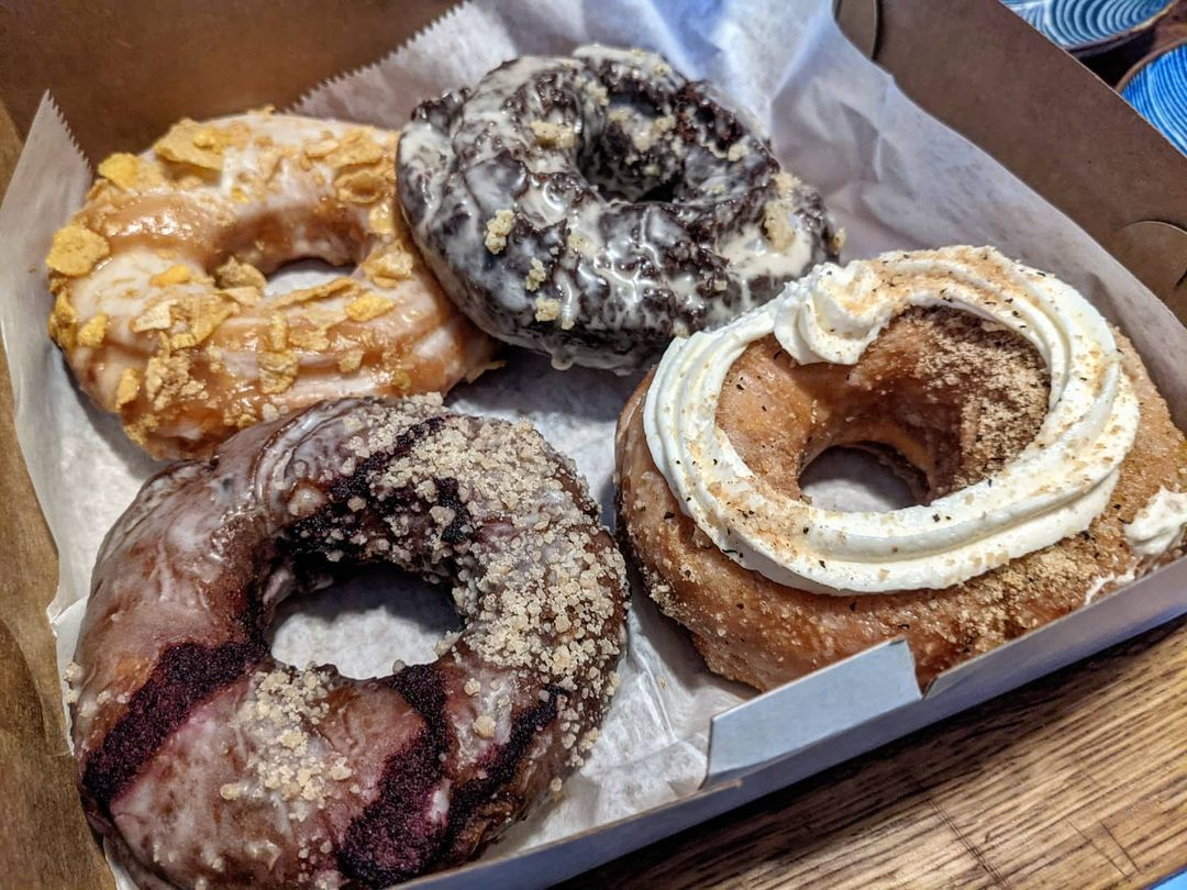 Four different doughnuts fill a cardboard box, each with a different type of glaze and topping.