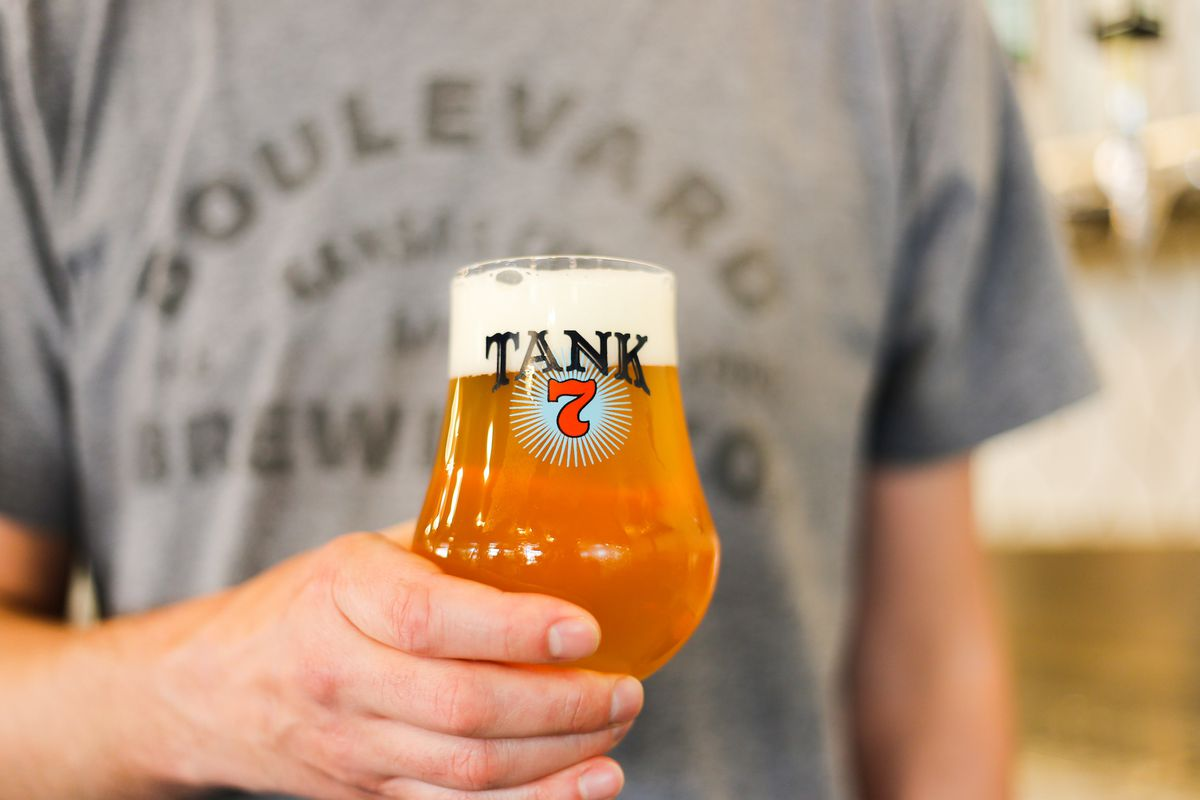 A man wearing a Boulevard Brewing Co. t-shirt holds a beer tulip glass.