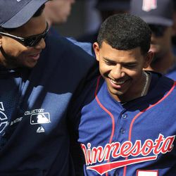 Minnesota Twins pitcher Esmerling Vasquez, left, embraces teammate Eduardo Escobar after Escobar scores during the eighth inning of a baseball game against the Detroit Tigers at Comerica Park in Detroit, Sunday, Sept. 23, 2012.