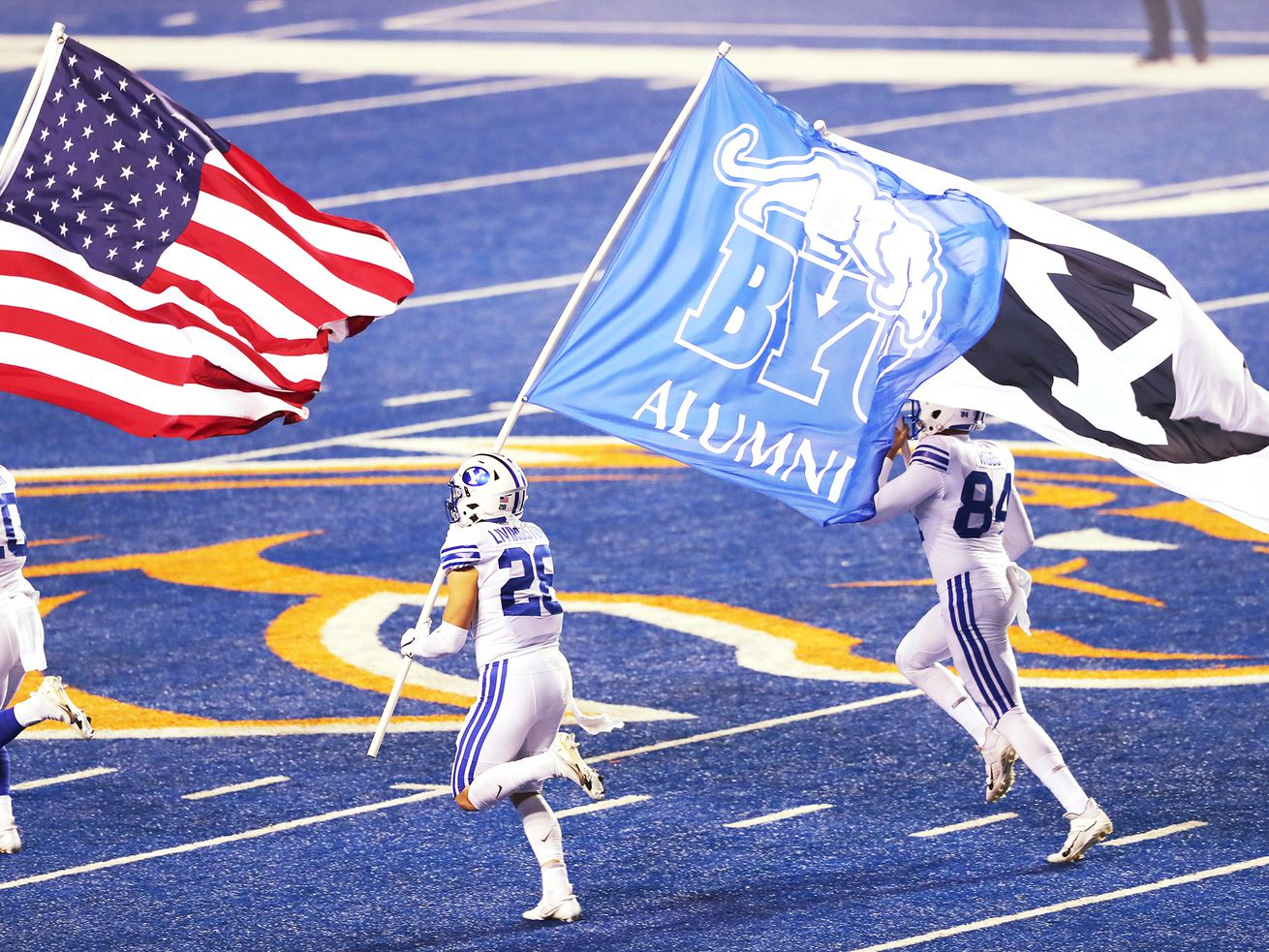 BYU defensive back Morgan Pyper (10), BYU defensive back Hayden Livingston (28) and BYU long snapper Austin Riggs (84) carry the flags out as BYU and Boise State play a college football game at Albertsons Stadium in Boise on Friday, Nov. 6, 2020.