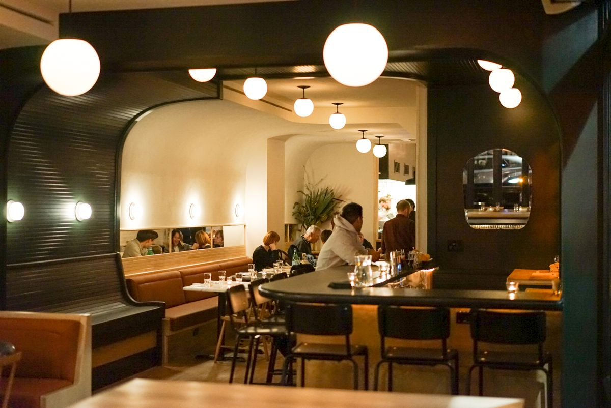 A dining room with a bar to the right and beige banquettes to the left, with people sitting in the back.