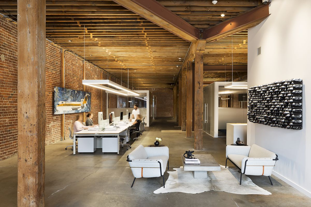 A space with rough wooden timbers, brick walls, and concrete floors holds a modern, open-plan office with frosted glass conference rooms.