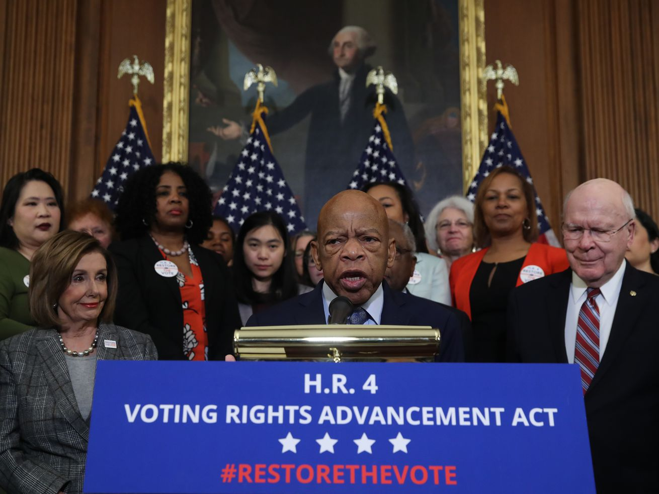 """Lewis speaks surrounded by US flags and Democratic lawmakers at a podium with a sign that reads """"HR 4 Voting Rights Advanced Act."""""""