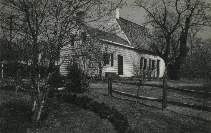 The exterior of a house. There is white siding and a thatched roof. There is a wooden fence, lawn, and trees that surround the house.