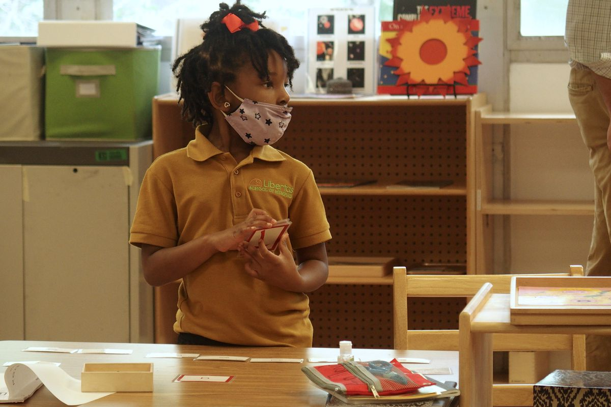 An elementary school student in class wearing a mask