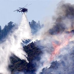 A helicopter drops water on flames atop a mountain above New Harmony on Sunday. Eleven structures burned over the weekend, but no injuries have been reported.