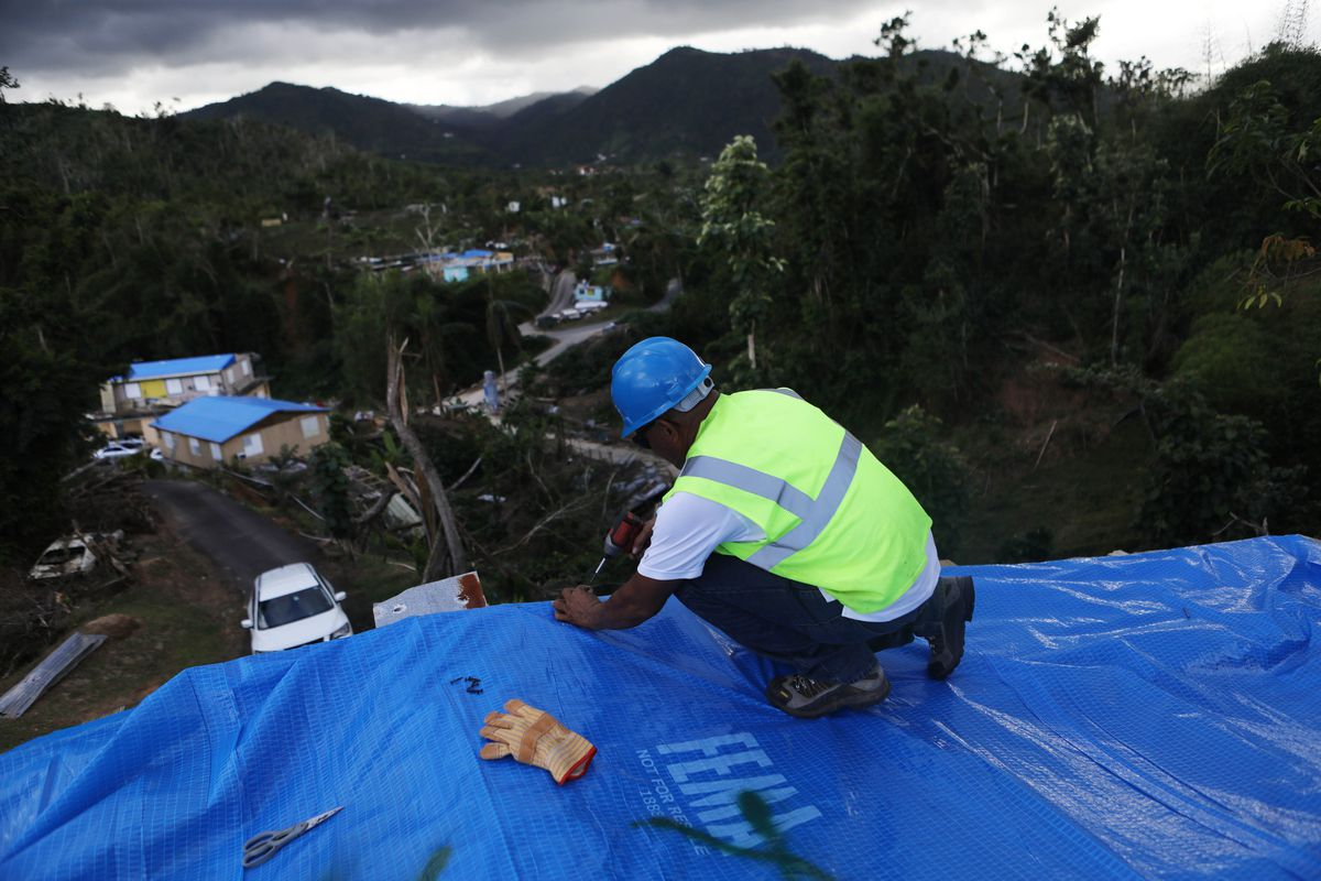 A contractor applies a FEMA tarp to a home damaged by Hurricane Maria in Puerto Rico.