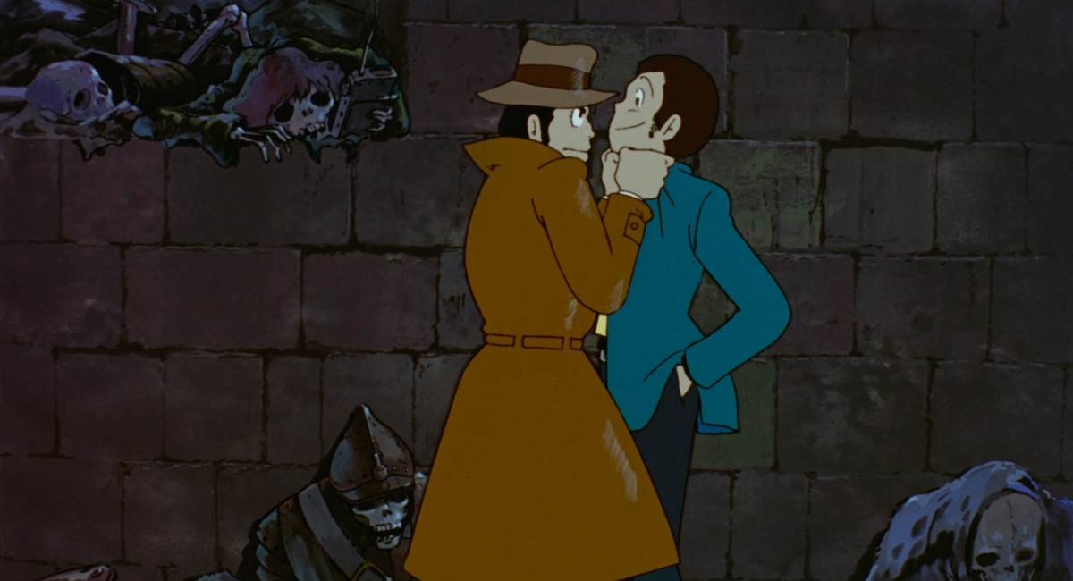 Interpol Inspector Zenigata holds master thief Lupin III by the lapels in a skeleton-filled crypt in The Castle of Cagliostro
