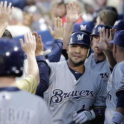 Milwaukee Brewers' Alex Gonzalez is high-fived by teammates after hitting a two-run home run in the second inning of a baseball game against the Atlanta Braves, Friday, April 13, 2012, in Atlanta.