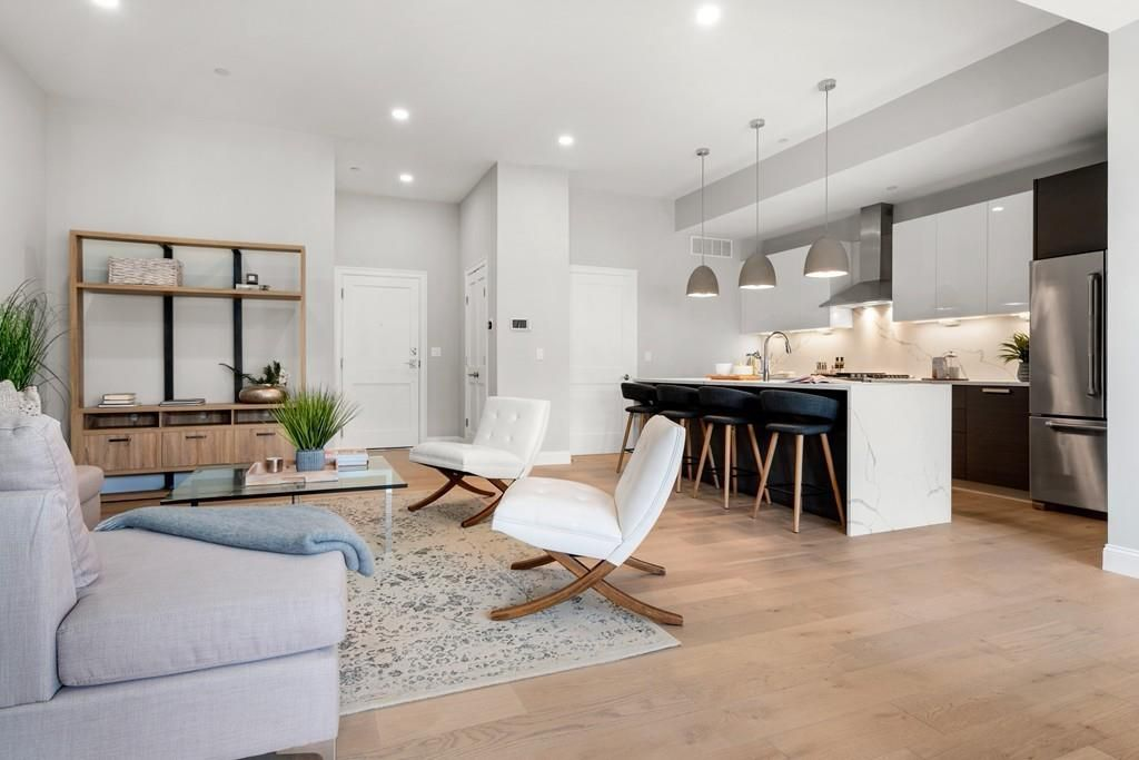 An open living room and kitchen with three stools in front of the kitchen's island.