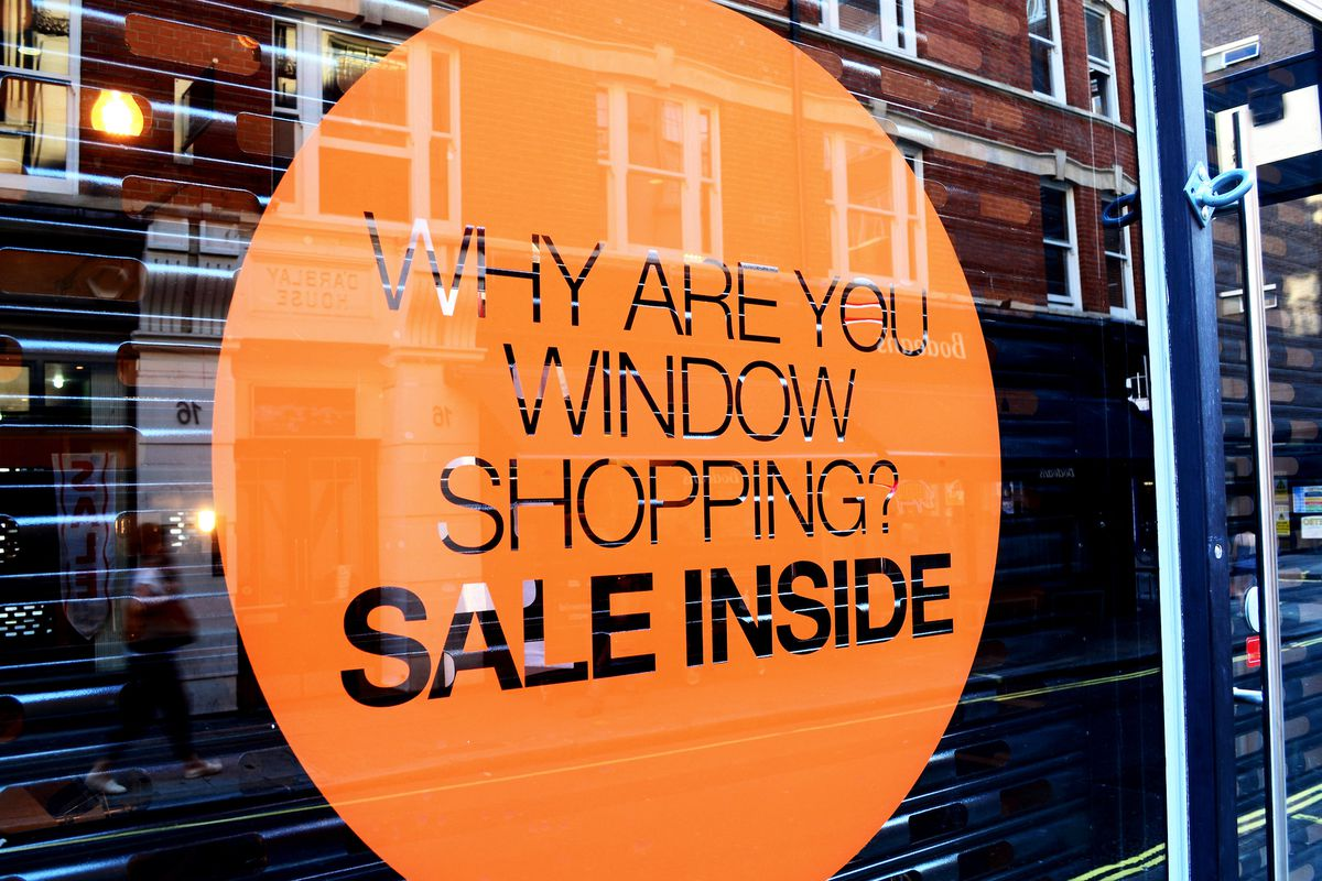 """A sign that reads """"Why Are You Window Shopping? Sale Inside"""""""